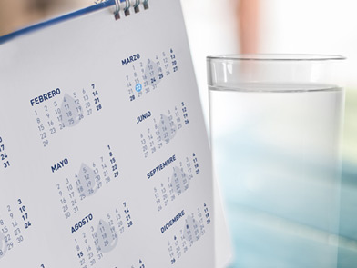 calendar next to a glass of water